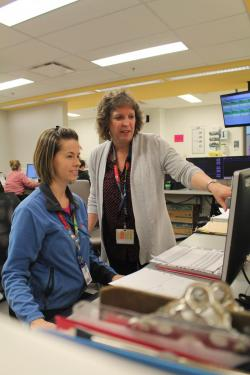 Kelly Anne Goudreau, Assistant Head Nurse, B8, and Susan consult the Tableau de lit to review the latest information on patient admissions to the unit.