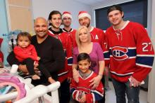 Mila (left) and her brother Lohan (middle) smile with mom, dad and the Montreal Canadiens.