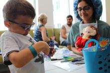 Having already named and gowned his teddy bear, Hoppy, 6-year old patient, Matteo prepares a special mask for Hoppy's upcoming surgery with help from Child Life Services intern, Afifah. He decides to colour the mask with markers and attach stickers of his favourite cars.