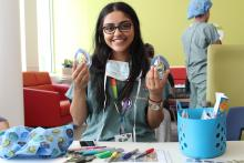 The Teddy Bear Clinic is officially open! Exam station 1 is coordinated by Child Life Services intern, Afifah, who holds up some teddy bear-sized masks ready to be decorated by patients.