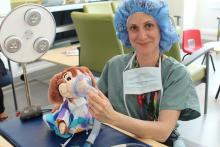 Exam station 3 is a teddy bear-sized version of an Operating Room Table coordinated by Child Life Specialist, Sabrina, who shows patients how to make sure a mask is properly fitted on each teddy bear before an operation.