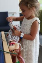 Tazia makes sure to hook her teddy bear up to an oxygen saturation machine to monitor his condition throughout the surgery.